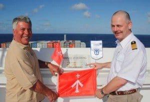 Dr. Peer Schmidt-Walther überreicht Kapitän Udo Wülms im Indischen Ozean Flagge und Ostsee-Zeitung auf der Brücke