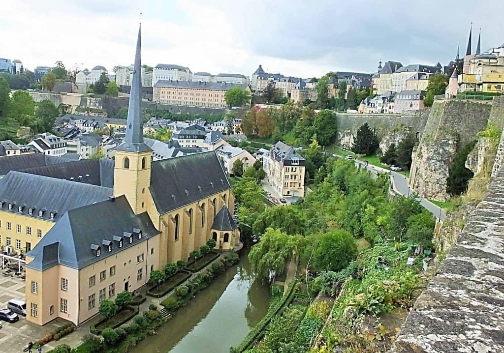 Blick von der begehbaren Festungsmauer über die im Flusstal gelegene frühere Abtei Neumünster auf die City von Luxemburg