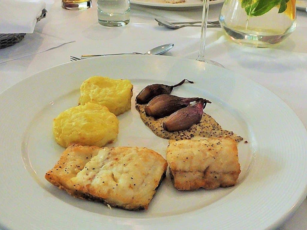"""Zu den Fischgerichten im Restaurant """"Brasserie"""" gehört auch Gebratener Dorsch, serviert auf Kartoffelgratin, dazu gebratene Zwiebeln und Senfsoße."""