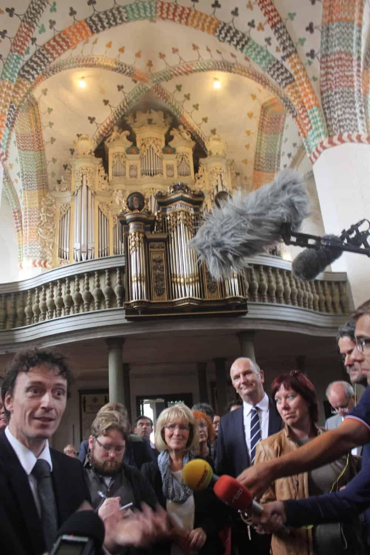Ministerpräsident Dietmar Woidke mit Pfarrer Bernhard Gutsche (l.) und Medienvertretern in St. Nikolai Jüterbog